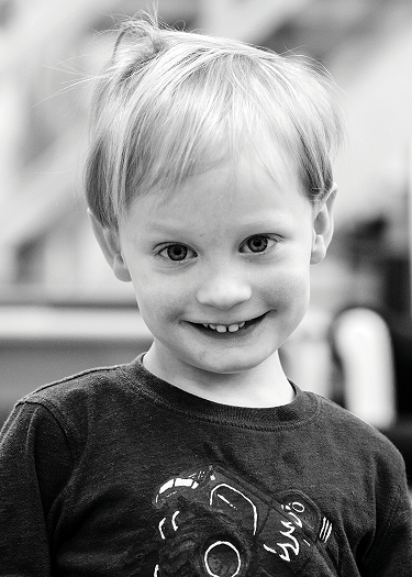 A black and white photo of Fitz, a student at Rosen Family Preschool. They have short blonde hair and light skin. They are looking at the camera and smiling.