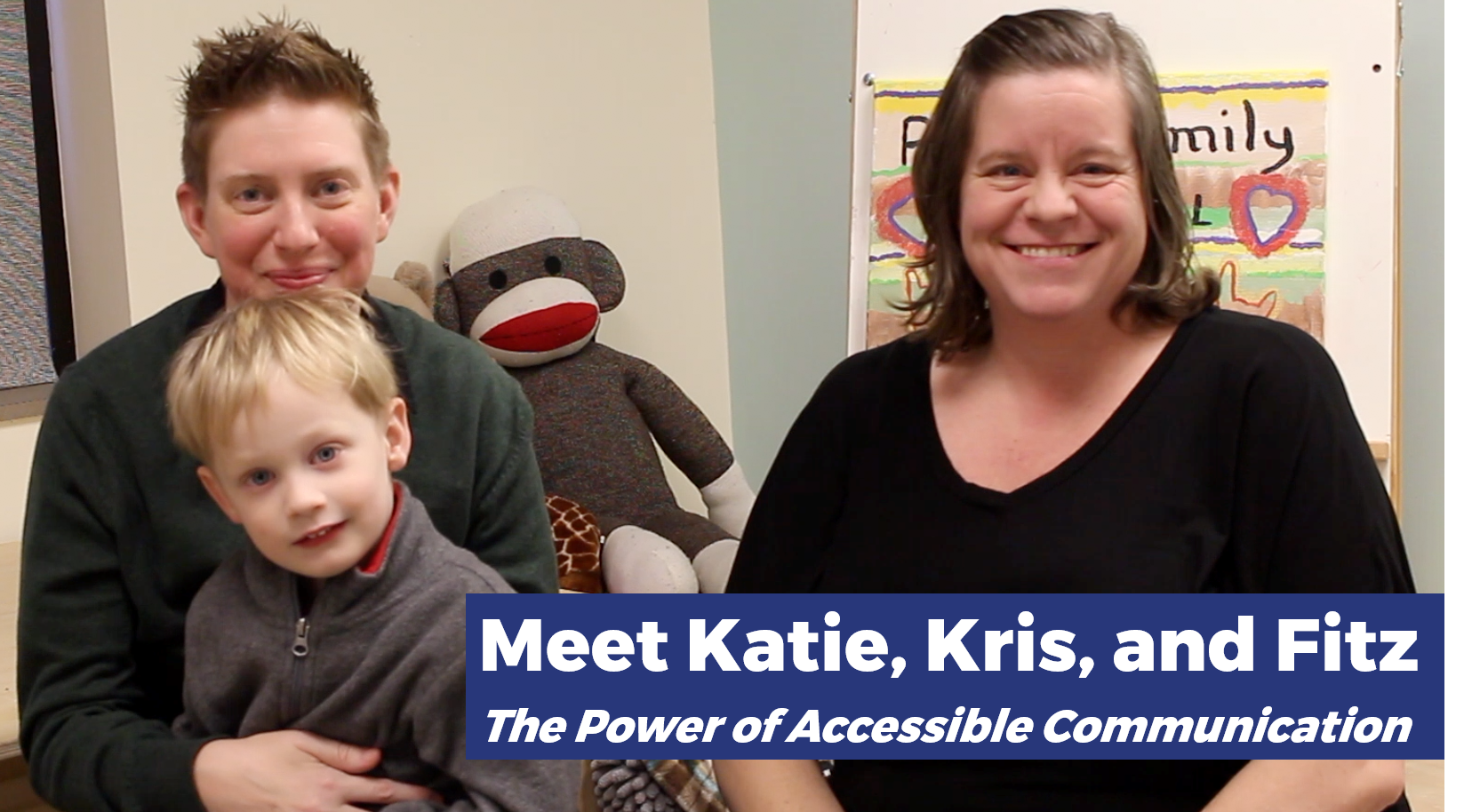 "Katie, Kris, and Fitz smiling for the camera. Two adults and one child sitting in a classroom. The adult on the left has short, spiky light brown hair with light skin and a dark gray sweater. They are sitting with the child, who has short, straight blonde hair with a gray sweater. The person on the right has brown hair down to their shoulders and light skin, with a black blouse. In the bottom right, blue bars have the text: ""Meet Katie, Kris, and Fitz / The Power of Accessible Communication""."