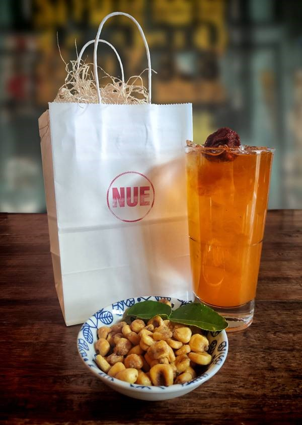 A photo of a bag, cocktail in a glass, and small bowl of nuts. The bag is paper, with the name Nue on the front. The orange cocktail is in a standard glass with ice. The nuts are in a blue and white bowl with a decorative leaf.